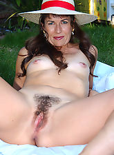 Muscular MILF displays her hairy pussy at the park